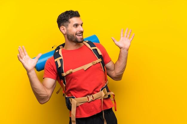 Homem jovem alpinista com expressão facial de surpresa