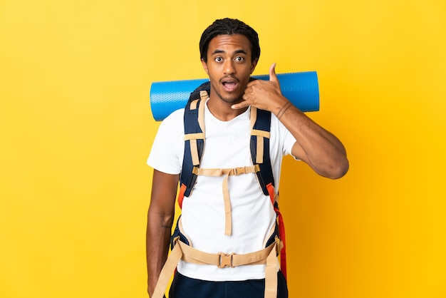 Homem jovem alpinista com tranças com uma grande mochila isolada em fundo amarelo, fazendo gesto de telefone. ligue-me de volta sinal