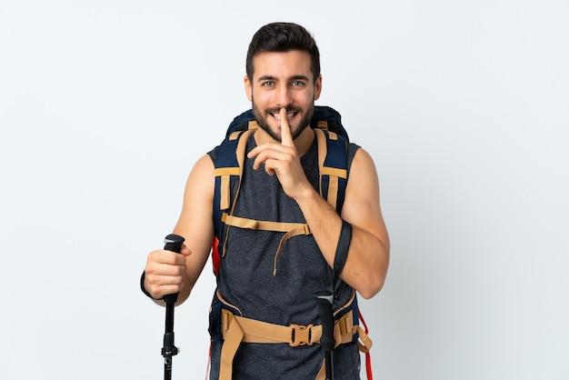 Homem jovem alpinista com uma mochila grande e pólos de trekking na parede branca, fazendo o gesto de silêncio