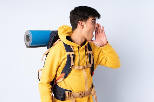 Homem jovem alpinista com uma mochila grande muro azul gritando com a boca aberta