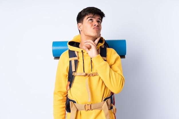 Homem jovem alpinista com uma mochila grande muro azul pensando uma idéia