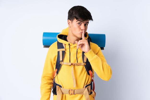 Homem jovem alpinista com uma mochila grande sobre azul isolado, fazendo o gesto de silêncio