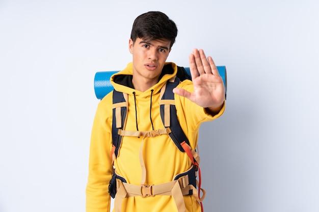 Homem jovem alpinista com uma mochila grande sobre parede azul, fazendo o gesto de parada com a mão