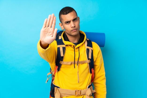 Homem jovem alpinista com uma mochila grande sobre parede azul isolada, fazendo o gesto de parada com a mão