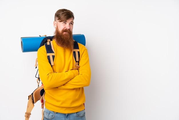 Homem jovem alpinista com uma mochila grande sobre parede branca, pensando em uma idéia