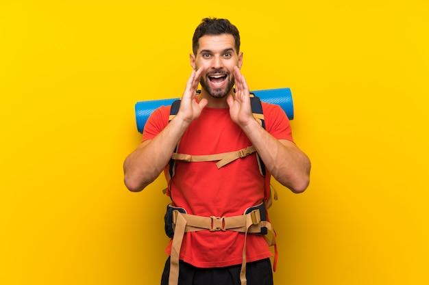 Homem jovem alpinista gritando com a boca aberta