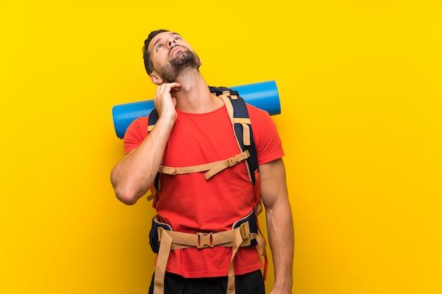 Homem jovem alpinista pensando uma idéia