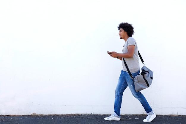 Homem jovem, andar, com, saco, e, telefone pilha