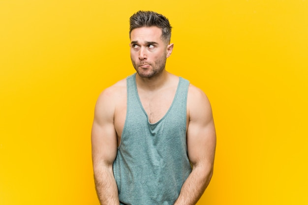 Homem jovem aptidão contra um fundo amarelo confuso, sente-se duvidoso e inseguro.