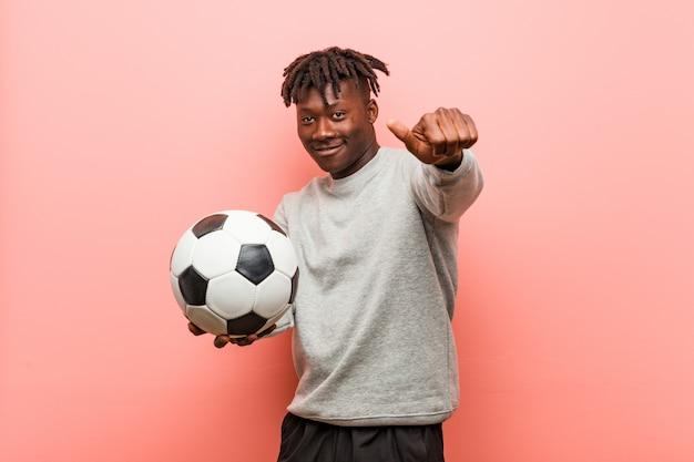 Homem jovem aptidão preto segurando um sorriso alegre de bola de futebol, apontando para a frente.