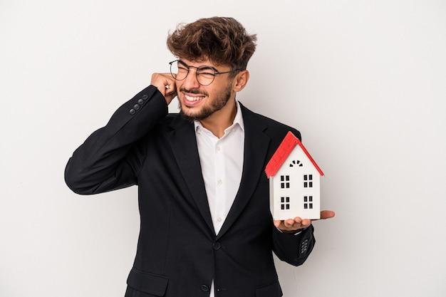 Homem jovem árabe imobiliário segurando uma casa modelo isolada no fundo isolado, cobrindo as orelhas com as mãos.