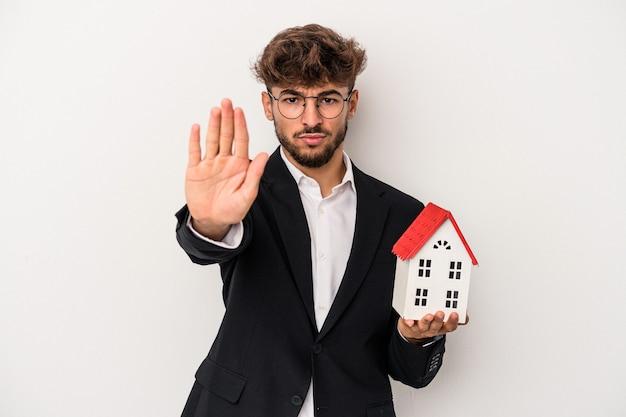Homem jovem árabe imobiliário segurando uma casa modelo isolada no fundo isolado em pé com a mão estendida, mostrando o sinal de pare, impedindo você.