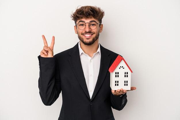 Homem jovem árabe imobiliário segurando uma casa modelo isolada no fundo isolado, mostrando o número dois com os dedos.