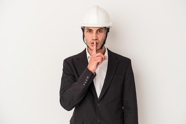 Homem jovem arquiteto caucasiano isolado no fundo branco, mantendo um segredo ou pedindo silêncio.