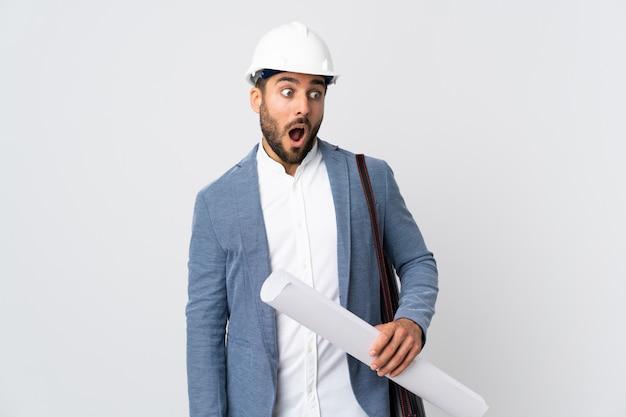 Homem jovem arquiteto caucasiano sobre parede branca isolada