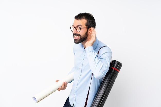 Homem jovem arquiteto com barba, ouvindo algo, colocando a mão na orelha