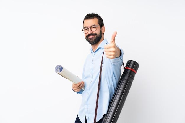 Homem jovem arquiteto com barba sobre parede branca isolada com polegares para cima porque algo bom aconteceu