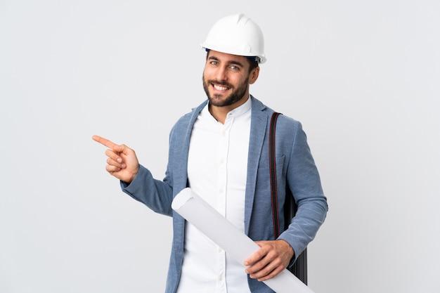 Homem jovem arquiteto com capacete e segurando plantas isoladas na parede branca, apontando o dedo para o lado