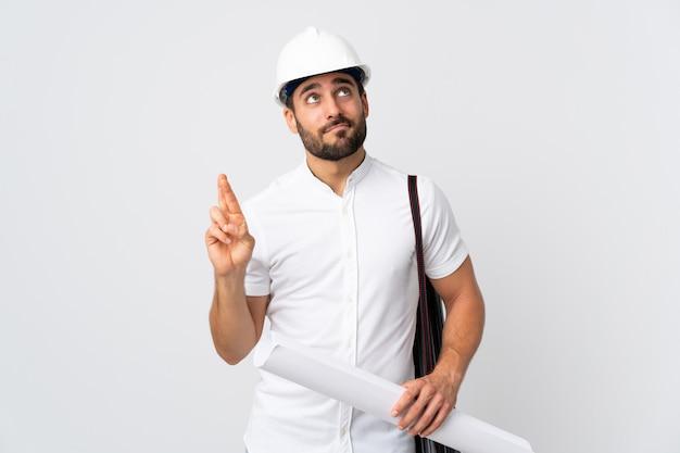 Homem jovem arquiteto com capacete e segurando plantas isoladas na parede branca com dedos cruzando e desejando o melhor