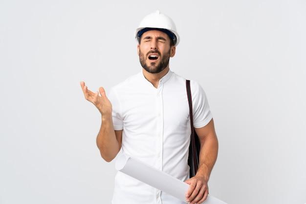 Homem jovem arquiteto com capacete e segurando plantas isoladas na parede branca estressado oprimido