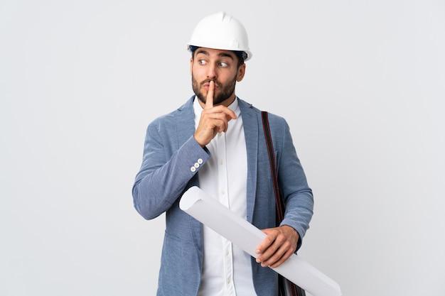 Homem jovem arquiteto com capacete e segurando plantas isoladas na parede branca, mostrando um sinal de gesto de silêncio colocando o dedo na boca
