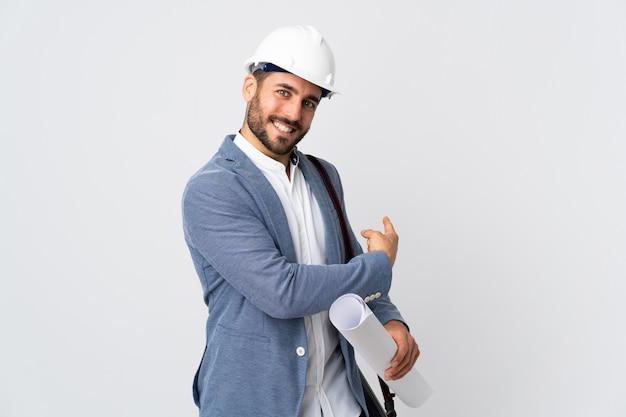 Homem jovem arquiteto com capacete e segurando plantas na parede branca, apontando para trás