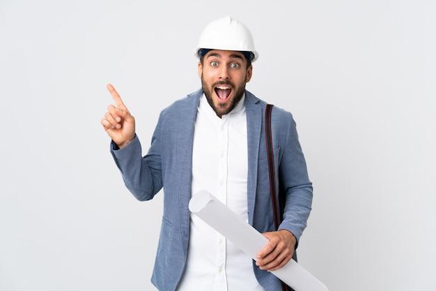 Homem jovem arquiteto com capacete e segurando plantas na parede branca surpreendeu e apontando o dedo para o lado