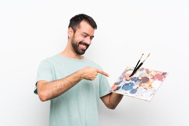 Homem jovem artista feliz segurando uma paleta