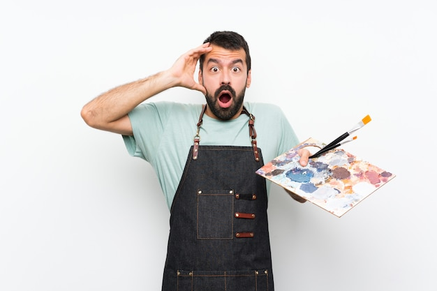 Homem jovem artista segurando uma paleta com expressão de surpresa