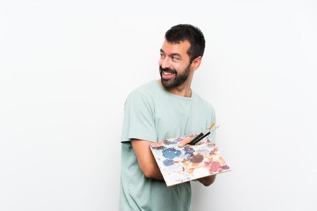 Homem jovem artista segurando uma paleta com os braços cruzados e feliz