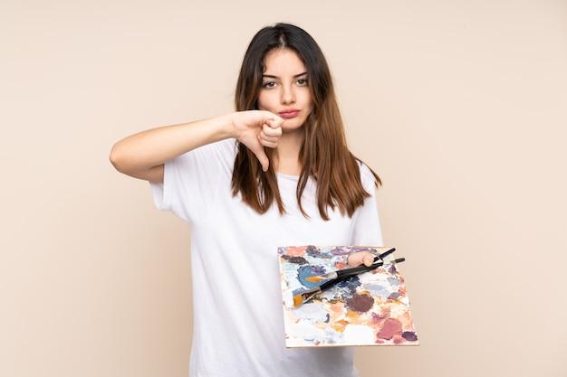 Homem jovem artista segurando uma paleta isolada em bege, mostrando o polegar para baixo sinal