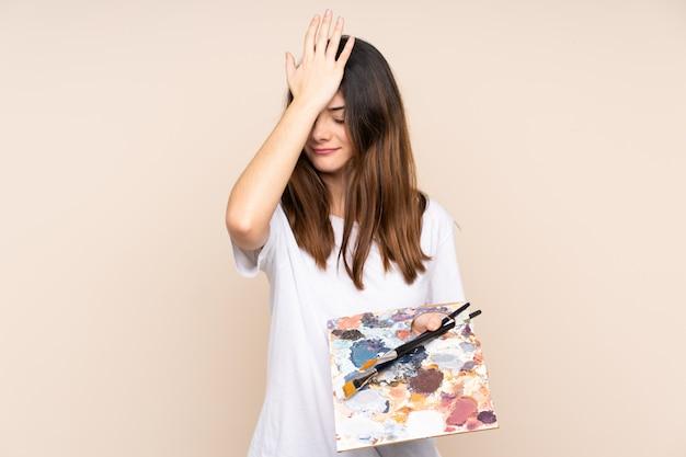 Homem jovem artista segurando uma paleta isolada em bege, tendo dúvidas com a expressão do rosto confuso