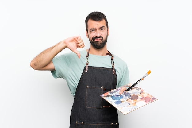 Homem jovem artista segurando uma paleta mostrando o polegar para baixo