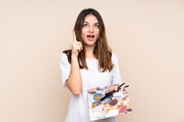 Homem jovem artista segurando uma paleta na parede bege, apontando com o dedo indicador uma ótima idéia
