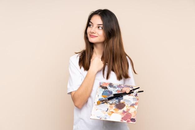Homem jovem artista segurando uma paleta na parede bege, pensando em uma idéia