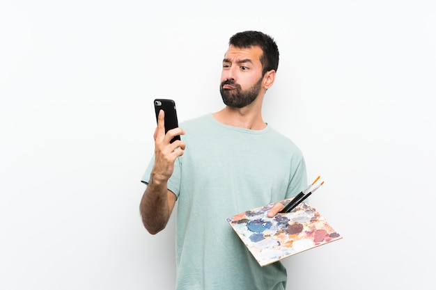 Homem jovem artista segurando uma paleta pensando e enviando uma mensagem