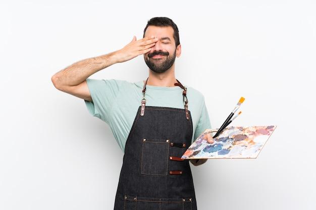 Homem jovem artista segurando uma paleta sobre fundo isolado, cobrindo os olhos pelas mãos
