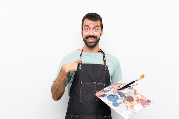 Homem jovem artista segurando uma paleta sobre fundo isolado, com expressão facial de surpresa
