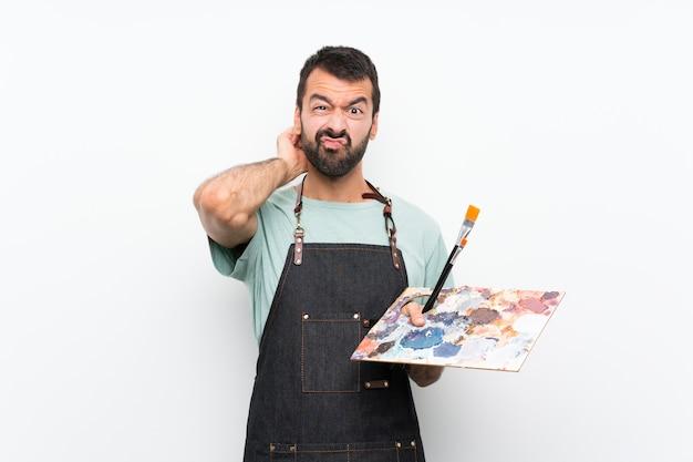 Homem jovem artista segurando uma paleta sobre parede isolada, tendo dúvidas