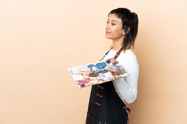 Homem jovem artista segurando uma paleta sobre parede, olhando para o lado