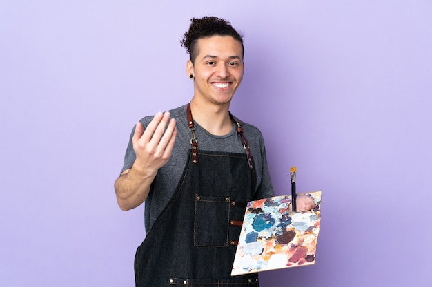 Homem jovem artista segurando uma paleta sobre roxo isolado, convidando a vir com a mão. feliz que você veio