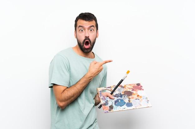 Homem jovem artista segurando uma paleta surpreso e apontando o lado
