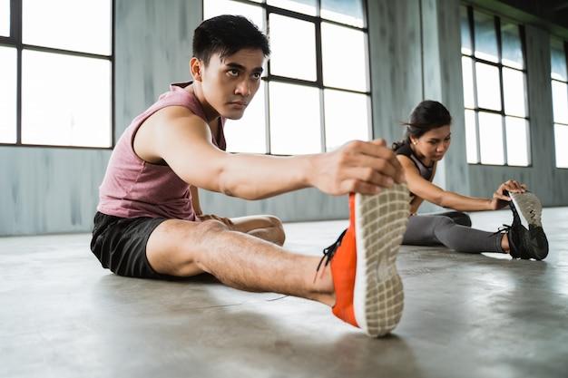 Homem jovem asiático fazendo pernas alongamento antes do exercício do núcleo