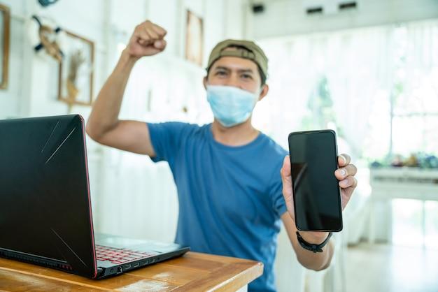 Homem jovem asiático freelance feliz usando máscara facial, trabalhando com computador laptop e show de telefone celular