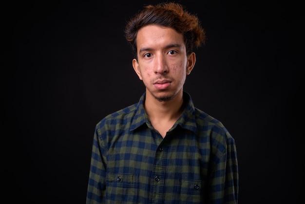 Homem jovem asiático hippie com cabelo encaracolado e acne contra o espaço negro