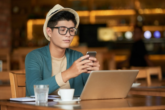 Homem jovem asiático hipster sentado no café com laptop e usando o smartphone