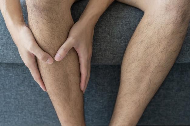 Homem jovem asiático irreconhecível sentado no sofá da sala e tocando em sua perna, machucou a perna.