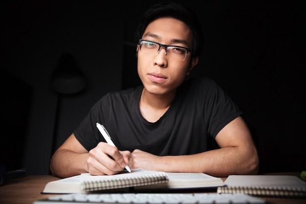 Homem jovem asiático sério entediado de óculos, aprendendo e escrevendo à noite em casa