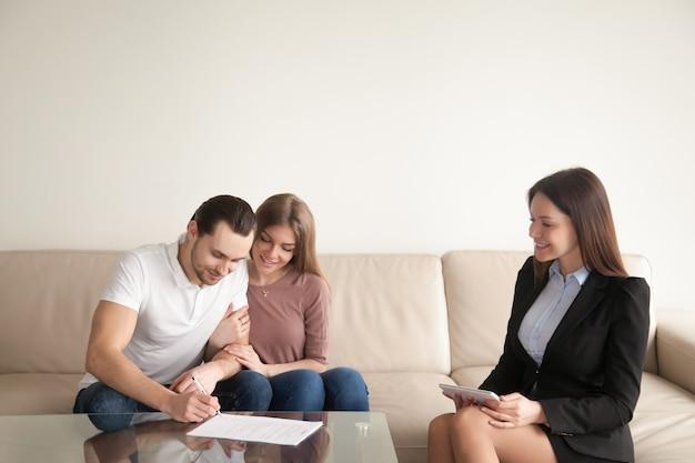 Homem jovem, assinando, papeis, sentando, perto, esposa, e, corretor de imóveis