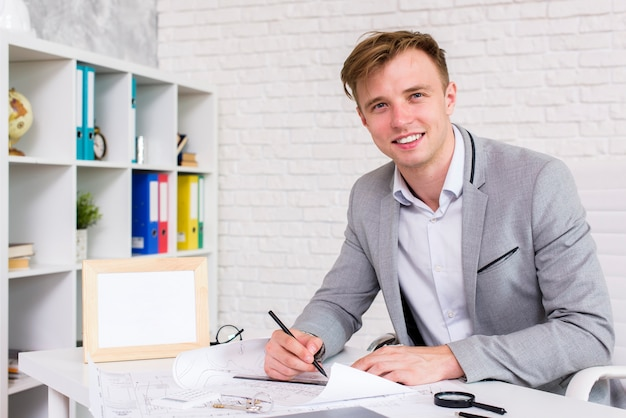 Homem jovem, assinando, um, documento, enquanto, olhando câmera